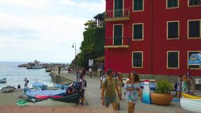 Italy, Monterosso - august, 2020. People in medical masks walk along the waterfront of the city of Monterosso. Houses, wooden