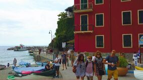 Italy, Monterosso - august, 2020. People in medical masks walk along the waterfront of the city of Monterosso.