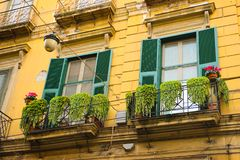 Savona Yellow Building with Iron Balconies and Bright Green Plants, Picturesque Neighborhood, Travel Italy. Italy, November, 2017 - Savona yellow building, iron Royalty Free Stock Images