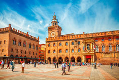 Italy Piazza Maggiore in Bologna old town. Tower of hall with big clock and blue sky on background. Antique buildings terracotta galleries Stock Photo