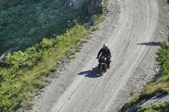 Single vintage motorbike riders in landscape. Italy Piedmont Alps circa July 2015 Motorbiker riding on vintage bike mountain road with hairpin bends Stock Image