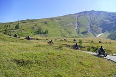 Group of vintage motorbike riders in landscape. Italy Piedmont Alps circa July 2015 Motorbikers riding on vintage bike mountain road with hairpin bends  blue sky Royalty Free Stock Photos
