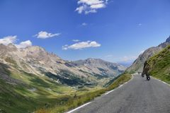 Group of vintage motorbike riders in landscape. Italy Piedmont Alps circa July 2015 Motorbikers riding on vintage bike mountain road with hairpin bends  blue sky Royalty Free Stock Image