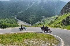 Group of vintage motorbike riders in landscape. Italy Piedmont Alps circa July 2015 Motorbikers riding on vintage bike mountain road with hairpin bends Stock Image