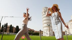 Italy, Pisa. Two young happy women in panamas walking on a background of the Leaning Tower of Pisa on a bright day