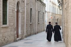 Italy, Puglia, Bari, Trani, a couple of priests. Italy, Puglia, Bari, Trani, a couple of young priests walk through the streets of the historic center royalty free stock image