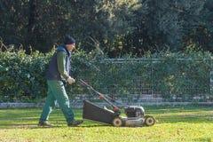 italy rome December 05, 2017: Mannen klipper gräs i trädgård y Arkivbilder