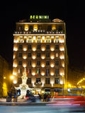 Italy, Rome - Hotel Bernini at Night from Across the Street. Hotel Bernini in Rome, Italy at night with fountain at the front and speeding cars across the frame royalty free stock image