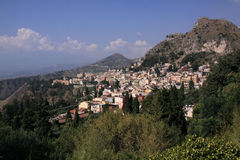 Italy Sicily Taormina from theatre. Italy Sicily Taormina old town and cloud covered Etna volcano in the distant left -  panoramic view from the amphitheatre Stock Image