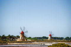Italy Sicily Two Old Windmills near salt lake. These old wind mills near Trapani in Sicily, Italy were used to pump seawater. This was stored in ponds and let to Stock Photos