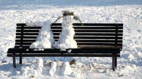 2012 Italy, snowmen on a park bench melt in the sun Stock Photo