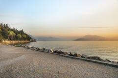 italy Solnedgång på sjön Garda med sikter av fjällängarna Arkivbilder