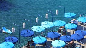 Italy Sorrento -view of a Jetty with blue sun shades. Scenic view of incidental people dining on a jetty with blue sun shades alongside the sea - seen from above stock photo