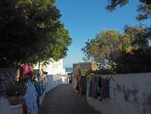 ITALY, STROMBOLI, JUNE 2, 2016: Street leading to port at Stromboli with colorful selling clothes hanging from the surrounding wa royalty free stock images