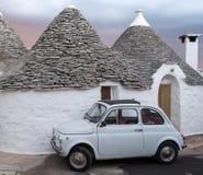 italy Traditionellt vitt tvättat trullihus med den vita bilen för Fiat tappningcinquecento som 500 framme parkeras, i Alberobello arkivbilder