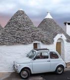 italy Traditionellt vitt tvättat trullihus med den vita bilen för Fiat tappningcinquecento som 500 framme parkeras, i Alberobello royaltyfria foton