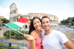 Italy travel couple with Italian flag by Colosseum. Embracing. Happy tourists lovers on honeymoon sightseeing having fun in front of Coliseum. Love and tourisn royalty free stock images