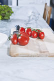 Italy, Tuscany, Magliano, Bunch of tomatoes on chopping board with knife Stock Image