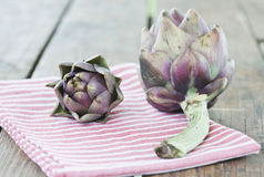 Italy, Tuscany, Magliano, Close up of artichokes with napkin on wooden table Stock Photo