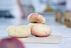 Italy, Tuscany, Magliano, Close up of flat peaches on chopping board Royalty Free Stock Photo