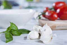 Italy, Tuscany, Magliano, Close up of garlic and herb with tomatoes on chopping board in background Stock Photo
