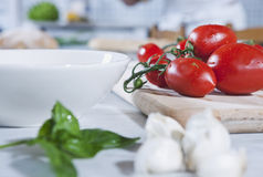Italy, Tuscany, Magliano, Close up of garlic and herb with tomatoes on chopping board in background Stock Photos