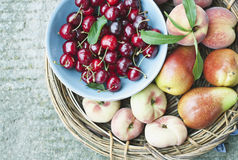 Italy, Tuscany, Magliano, Close up of peach pears and cherries in basket, elevated view Royalty Free Stock Photo