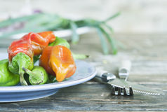 Italy, Tuscany, Magliano, Variety of chilli peppers in plate with cutlery on wooden table, close up Stock Image