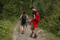 Italy, Valle d`Aosta, july 29 2017: two hikers walking on a path on the mountains. Italy, Valle d`Aosta, july 29 2017: two hikers walking in a wood on the Stock Photo