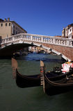 Italy Venice arched bridge and gondolas. Italy Venice Historical center - old arched bridge spanning a narrow canal with gondolas in the foreground royalty free stock images