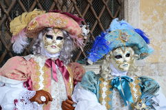 Italy, Venice Carnival: noble couple. Noble couple wearing masks with complex decoration and an outfit in orange and blue-green, medieval style Royalty Free Stock Images