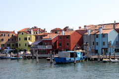 Italy. Venice. Colored red, yellow, blue houses near water and boats on blue sky background, horizontal view. Royalty Free Stock Photography