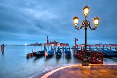 Italy, Venice Embankment at night. Historical lamp post with goldolas and San Giorgio di Maggiore on a rainy morning stock images