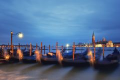 Italy, Venice Embankment at night. Historical lamp post with goldolas and San Giorgio di Maggiore on a rainy morning. Long exposure to show how the boats move stock images