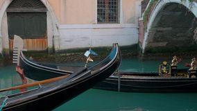 Italy, Venice - February, 2019: Picturesque gondola with two tourists is swimming out under bridge stock video footage