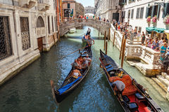 ITALY, VENICE - JULY 2012: Gondolas with tourists cruising a small Venetian canal on July 16, 2012 in Venice. Gondola is a major m Stock Photography