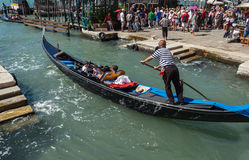 ITALY, VENICE - JULY 2012: Gondolas with tourists cruising a small Venetian canal on July 16, 2012 in Venice. Gondola is a major m Royalty Free Stock Image