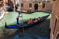 ITALY, VENICE - JULY 2012: Heavy traffic of gondolas with tourists cruising a small canal on July 16, 2012 in Venice. Gondola is a Stock Photos