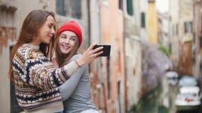 italy venice Tv? unga kvinnor som st?r p? den lilla bron och tar selfies p? en bakgrund av en vattenkanal lager videofilmer