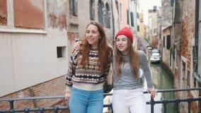 italy venice Två unga kvinnor som står på den lilla bron ovanför vattenkanalen och spännande omkring ser lager videofilmer