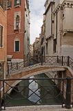 Italy Venice Typical foot bridge over canal. Italy Venice View of a small canal with curved foot bridge and houses Royalty Free Stock Photo