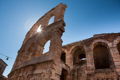 Italy, Verona, ancient amphitheater. Ancient wall and arch, bright rays of the sun, bright blue sky Royalty Free Stock Image