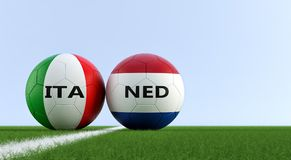 Italy vs. Netherland Soccer Match - Soccer balls in Italy and Netherlands national colors on a soccer field. Royalty Free Stock Image