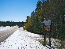 Itasca State Park in Minnesota, USA is source of Mississippi River. This is a snow covered road sign at the north entrance to the park on a sunny day stock photo