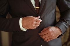 Item male costume. Men's hands in a brown suit buttoned button stock image