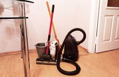 Items for cleaning the house. Vacuum cleaner, two mops and a plastic bucket with a rag stock photos
