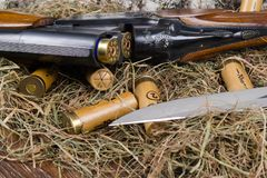 Items For Hunting In Dry Grass, Shells For A Gun And A Knife Royalty Free Stock Photography