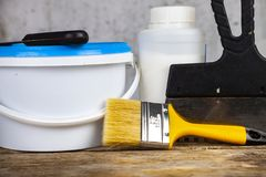 Items for home or office renovation. Against a gray wall. Paint can and brush on the table royalty free stock images
