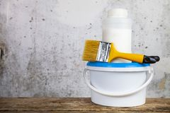 Items for home or office renovation. Against a gray wall. Paint can and brush on the table stock image