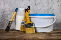 Items for home or office renovation. Against a gray wall. Paint can and brush on the table royalty free stock photos